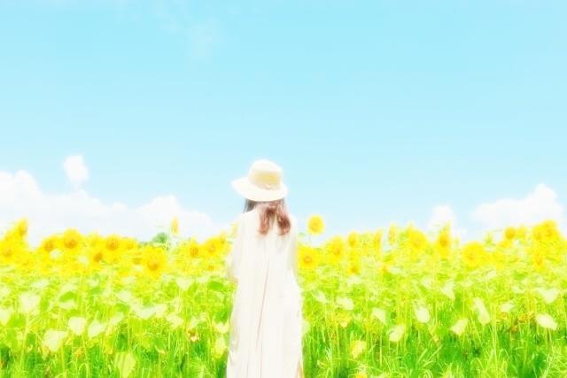 ひまわり畑に立つ女性
